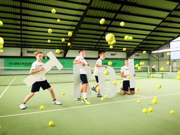 Tennisspieler mit Schriftzug Troi auf Tennisplatz