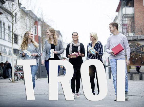 Menschen mit Stadtgutschein und Schriftzug Troi in der Troisdorfer Innenstadt