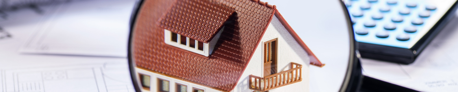 Haus in Fokus einer Lupe - Papiere