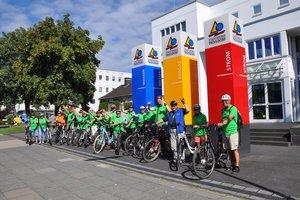 Menschen auf E-Bikes vor Stadtwerke Troisdorf Gebäude
